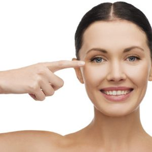 health, spa and beauty concept - clean face of beautiful young woman pointing to her eye